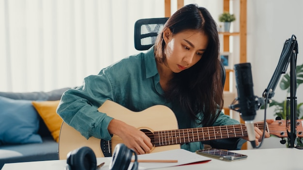 スマートフォンからアコースティックギターのリスニング曲を演奏する幸せなアジアの女性ソングライター
