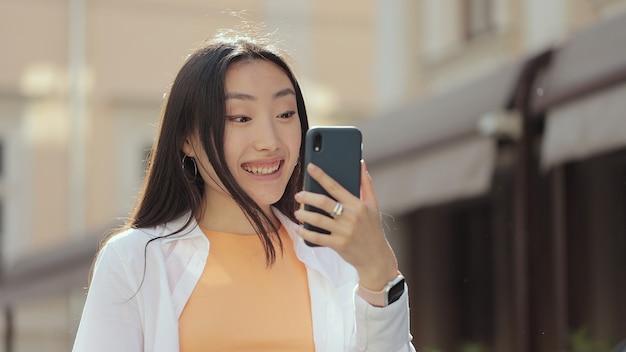 거리에서 화상 통화를 하는 행복한 아시아 여성, 도시에서 휴대전화로 화상 통화를 하는 여성