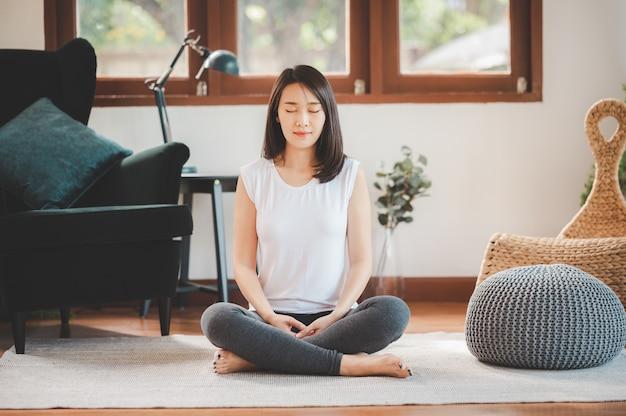 幸せなアジアの女性スポーティな魅力的な自宅で瞑想を練習