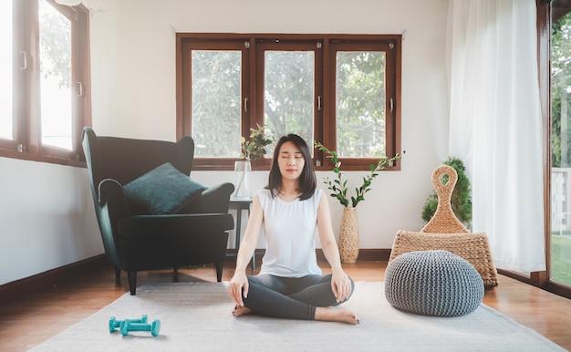 幸せなアジアの女性スポーティな魅力的な自宅のリビングルームでヨガ瞑想を練習