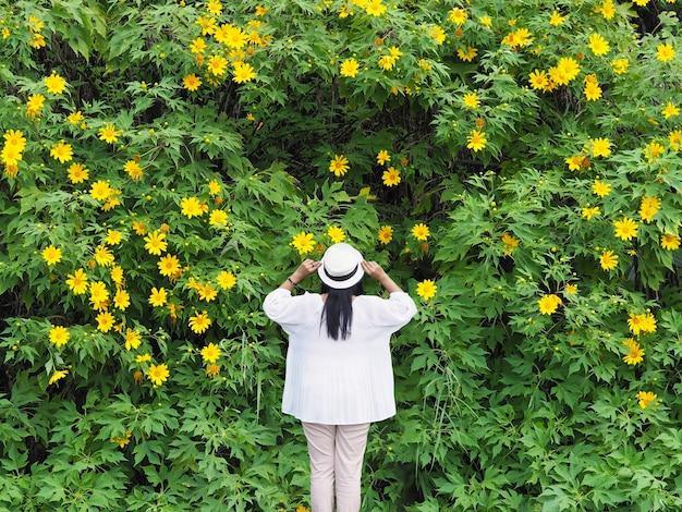 트리 메리 골드 또는 맥시 칸 해바라기 배경 위에 서 행복 아시아 여자.