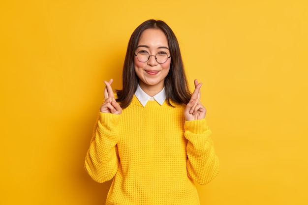 Happy asian woman stands with crossed fingers believes in good luck on exam hopes dreams come true wears round spectacles and casual sweater.