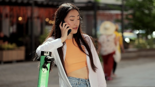 행복한 아시아 여성은 여름에 거리에서 전기 스쿠터를 타고 전화로 이야기하는 현대적인 전기 스쿠터와 함께 도시 거리에서 전화 통화를 하고 있습니다.
