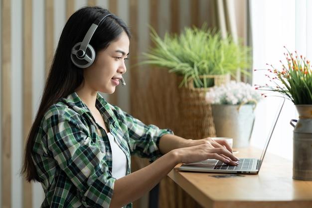 행복 한 아시아 여자 학생은 온라인 과정을 공부하는 hearphone을 착용하고 랩톱 컴퓨터를 사용하여 회의 화상 통화로 의사 소통