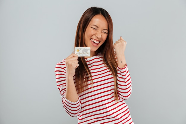 Happy asian woman in sweater rejoice and holding credit card over gray background