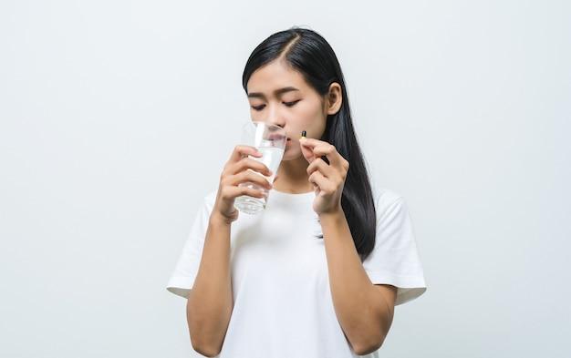 ピルを服用し、新鮮な水のガラスを保持している幸せなアジアの女性。