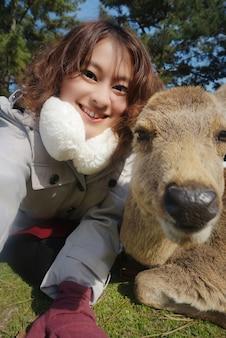 Счастливая азиатская женщина, делающая селфи-фотографию с оленями на лугу, девушка отдыхает в отпуске осенью в парке нара, япония