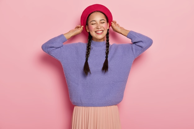Счастливая азиатская женщина трогает берет, приятно улыбается, показывает белые зубы, имеет две косички, носит фиолетовый свитер и юбку, выражает приятные чувства, изолирована от розовой стены