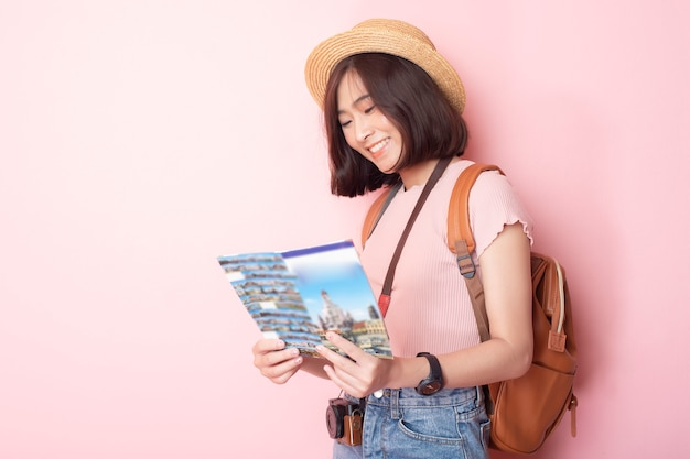 Happy asian woman tourist on pink wall