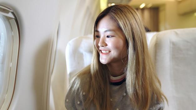 Счастливое азиатское путешествие женщины в самолете для туристического отдыха.