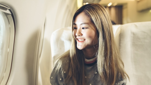 幸せなアジアの女性が飛行機で旅行