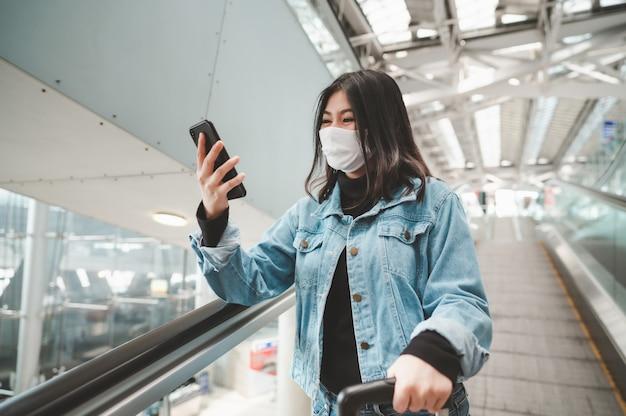 荷物を持ってエスカレーターに立っているスマートフォンを使用してコロナウイルスから保護するためのマスクを身に着けている幸せなアジアの女性旅行者