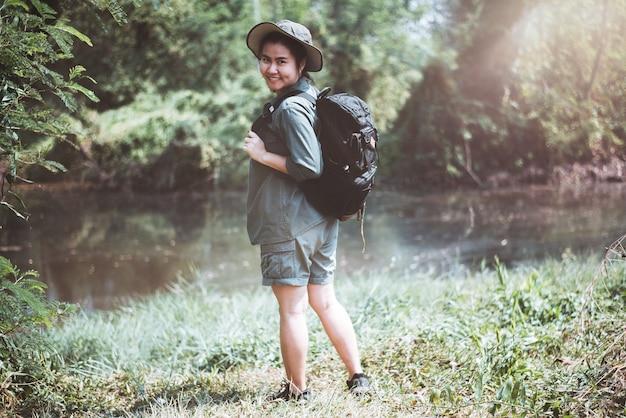 Счастливая азиатская женщина, путешествующая в лесу, летние каникулы на открытом воздухе