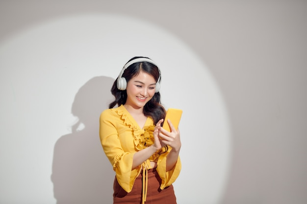 Happy asian woman using headphone and smartphone isolated