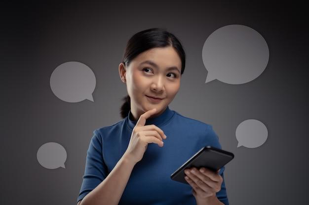 スマートフォンとアイコンホログラム効果を使用して幸せなアジアの女性