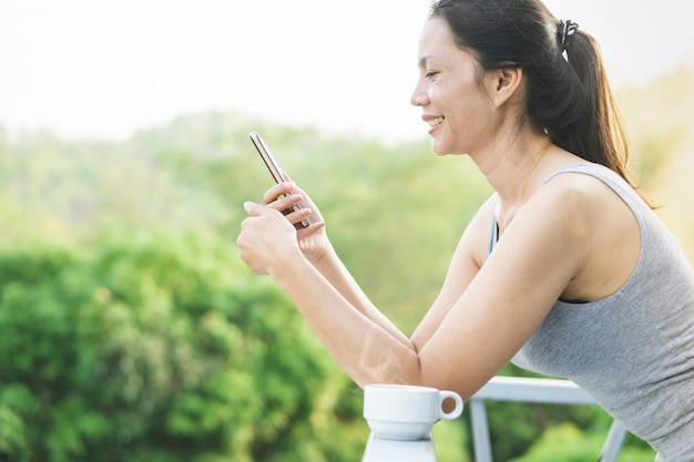 Happy asian woman using smart phone and drinking coffee