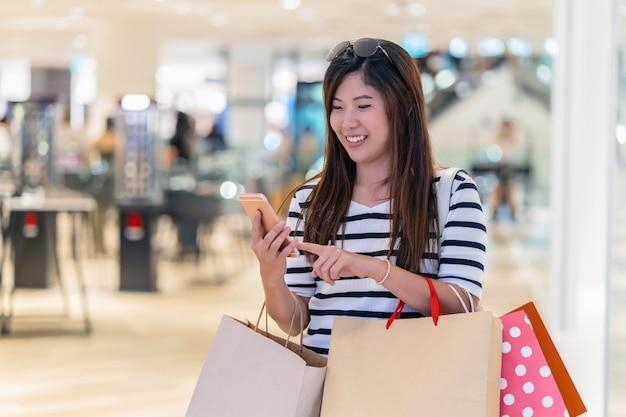스마트 휴대 전화를 사용하여 제품과 가격을 확인하는 행복 한 아시아 여자