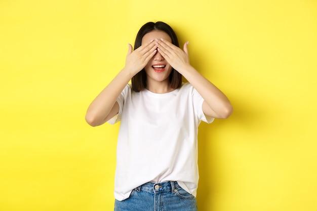 サプライズギフトを待っている幸せなアジアの女性、目を閉じて笑顔、何かを期待して、黄色の背景の上に立っています。