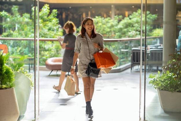 백화점에서 걸어와 쇼핑 가방을 들고 행복 아시아 여자