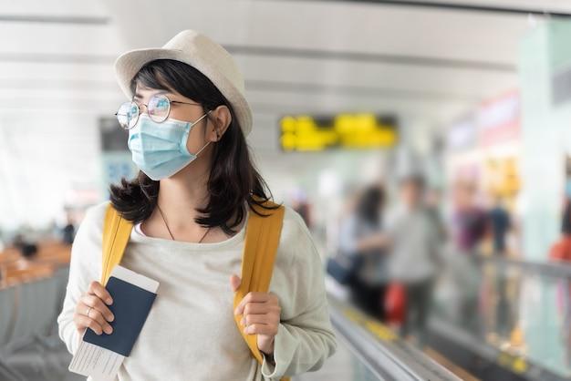 행복 한 아시아 여자는 바이러스 전염병 동안 국제 공항 터미널에서 걷는 보호 얼굴 마스크와 안경을 착용합니다.