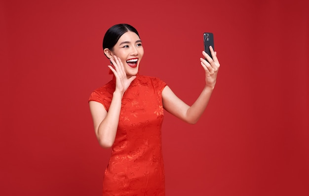 Happy asian woman wearing traditional cheongsam qipao dress having video-call with lover holding smart phone in hand shooting selfie on front camera on red.