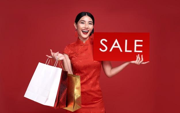 赤い壁に隔離の販売看板とショッピングバッグを保持している伝統的なチャイナドレスのチャイナドレスを着て幸せなアジアの女性。