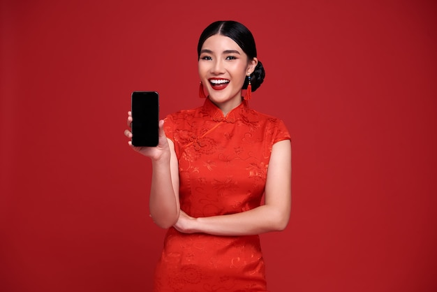 Happy asian woman wearing traditional cheongsam qipao dress showing mobile phone isolated on red background.