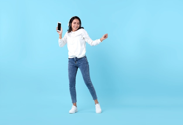 Happy asian woman wearing wireless headphone listening to music from smartphone on blue.
