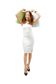 Happy asian woman in white dress carrying shopping bags standing