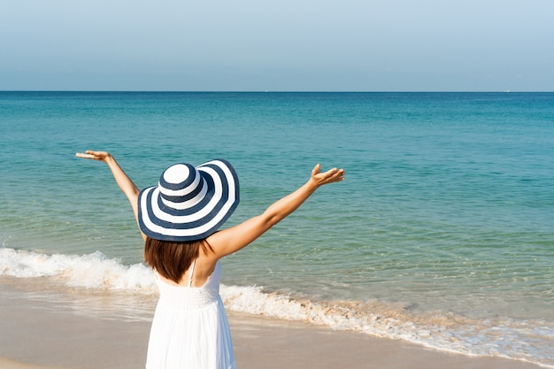 Happy asian woman in white dress enjoys at tropical beach on vacation. summer on beach concept.