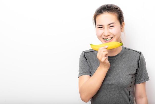 Счастливая азиатская женщина с подтяжками, держащая банан на белом