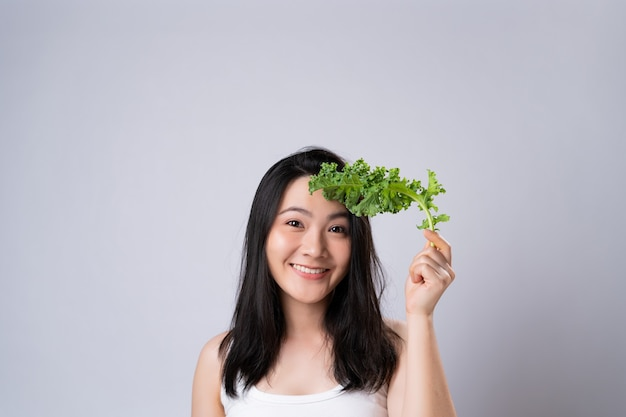 Happy asian woman with kale leaf isolated over white wall. healthy lifestyle with clean food concept.