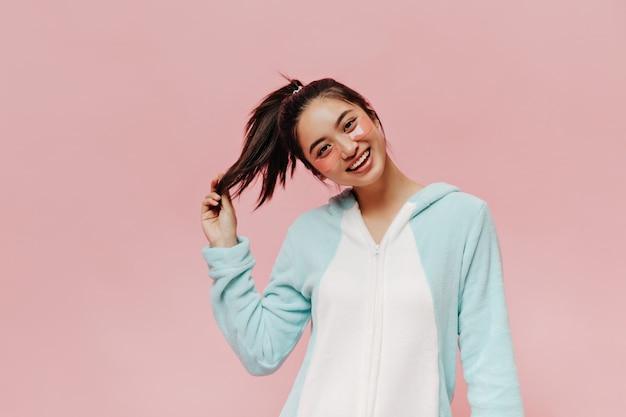 포니테일을 한 행복한 아시아 여성이 분홍색 벽에 진심으로 미소를 짓고 있다