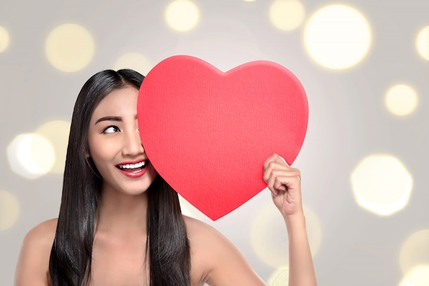 Happy asian woman with red heart in hand