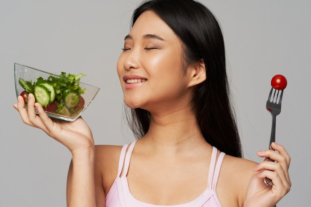 Happy asian woman with salad