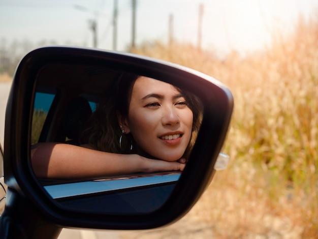자동차로 여행하는 짧은 머리를 가진 행복한 아시아 여성. 매력적인 여성 여행자들은 햇빛, 여름, 사이드 미러에서 볼 수 있는 외부 전망을 바라보며 웃고 있습니다.