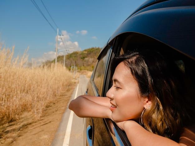 車で旅行する短い髪の幸せなアジアの女性。魅力的な女性旅行者は、夏の間、車の外、地元の道路、景色を見ながら笑顔で楽しんでいます。
