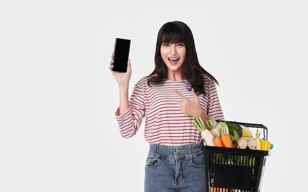 白い背景に分離された新鮮な野菜の食料品がいっぱい入ったかごを保持しているスマートフォンで幸せなアジア女。