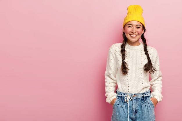 Happy asian woman with tender smile, keeps both hands in pockets on jeans, wears yellow hat, white jumper, has two pigtails poses over rosy wall blank space