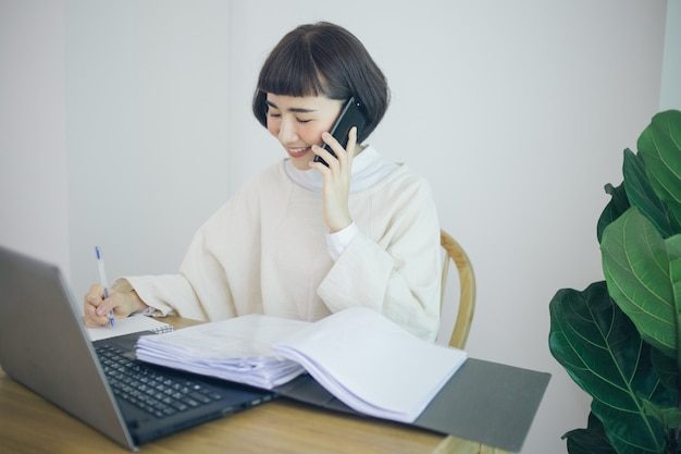 Счастливая азиатская женщина работая от дома она пользуется смартфоном, таплетом и почерком.