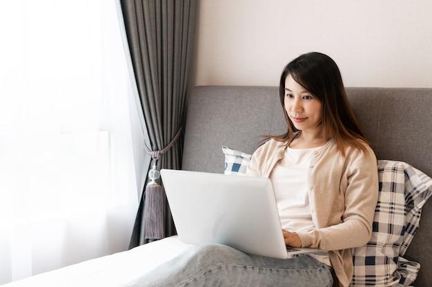 Счастливая азиатская женщина работает на ноутбуке, сидя на кровати. работа из дома концепции.