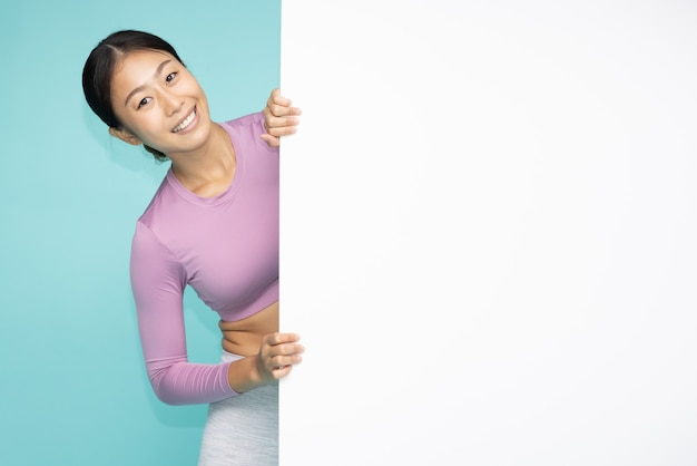 Happy asian woman in yoga suit standing behind blank white billboard
