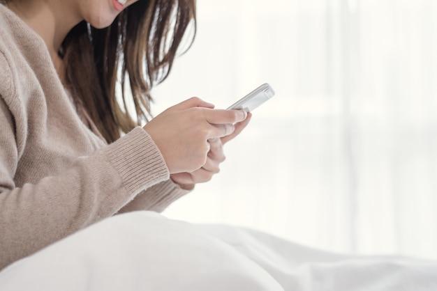 행복한 아시아 여성은 아침에 침대에서 스마트 폰을 사용하고 있습니다