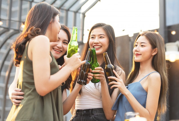 Happy asian women holding bottles of beer