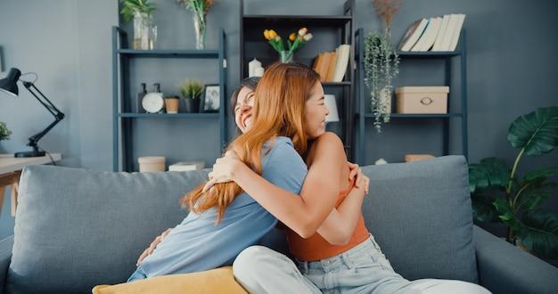幸せなアジアの女性のティーンエイジャーは、家で笑顔を抱きしめる彼女の親しい友人を訪問します
