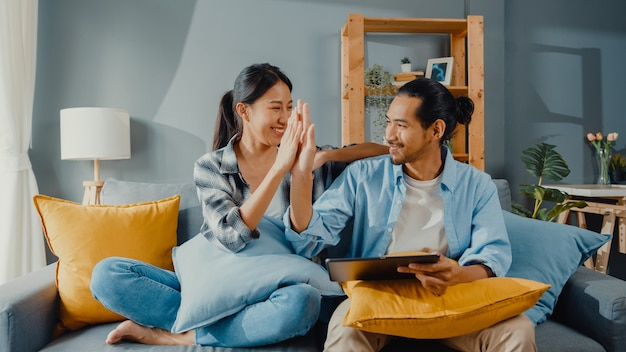 Happy asian young attractive couple man and woman sit on couch use tablet for shopping online furniture in new house