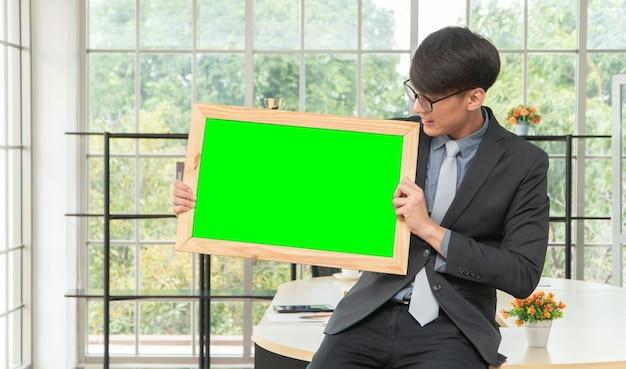 空のホワイトボードを保持し、オフィスのテーブルに座って幸せなアジアの青年実業家。広告、テキスト、およびコンテンツのコピースペースの概念。