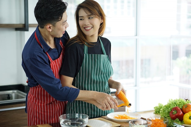 Happy asian young couple cooking food in the kitchen