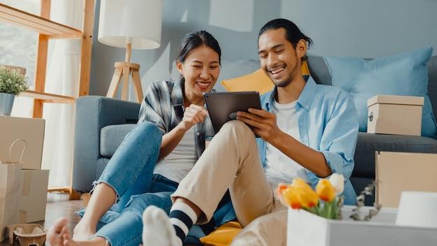幸せなアジアの若いカップルの男性と女性は、新しい家のカートンパッケージで家を飾るためにオンラインショッピング家具にタブレットを使用しています。