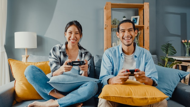 Happy asian young couple man and woman sit on couch use joystick controller for play video game